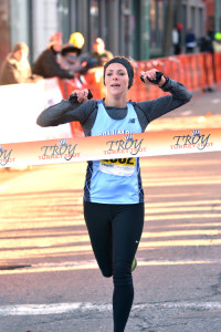 Nicole Blood breaks the tape first in the women's 10k with a time of 36:26 at the 66th Troy Turkey Trot on November 28, 2013. Photo Copyright 2013 Pat Hendrick Photography)
